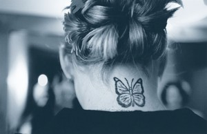 A girl displays a butterfly tatoo on her neck.